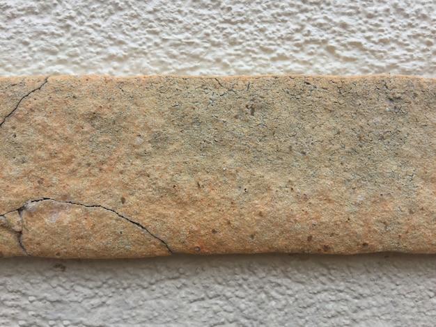 セメントの壁の背景に汚れたレンガのブロックに閉じます。