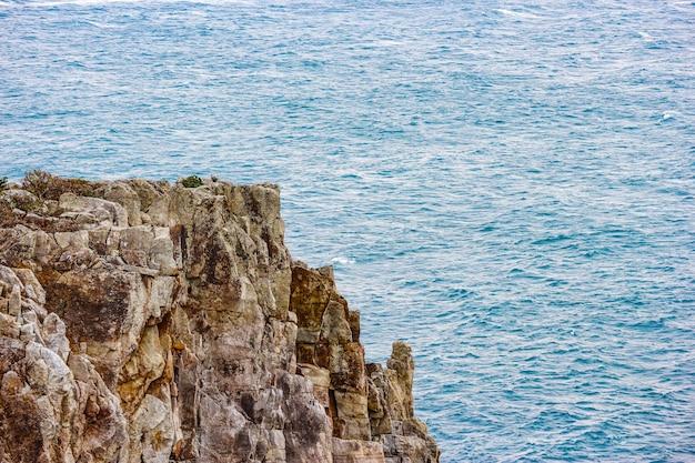 Санданбеки каменный скалы пляж с размахивая синим морем.