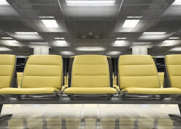Желтый ряд сидений ожидания для посадки в аэропорту.