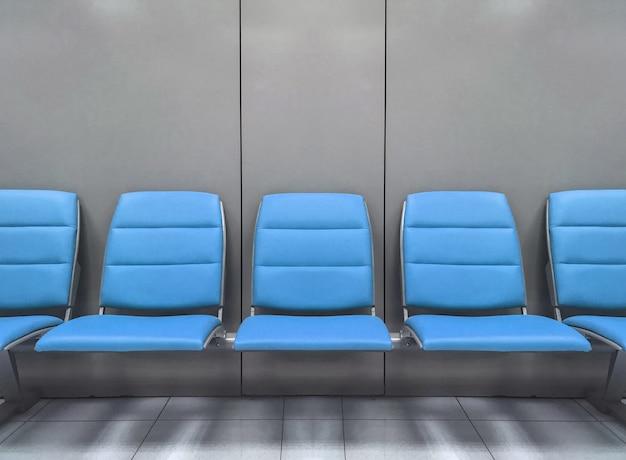 Синие сиденья ждут посадки в аэропорту.