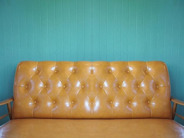Коричневый кожаный диван со старинной цветной деревянной панельной стеной.
