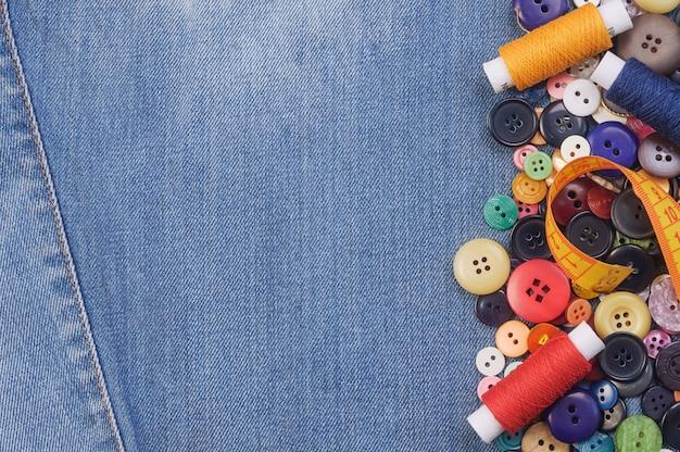 カラフルな縫製ボタン、黄色の巻き尺、糸巻き