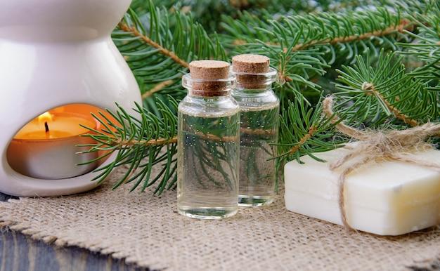 リネンナプキンの後ろにトウヒのエッセンシャルオイルのボトル、天然石鹸、モミの枝。