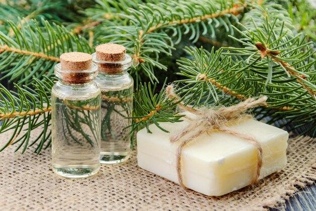 リネンナプキンにトウヒのエッセンシャルオイル、石鹸、モミの枝のボトル。