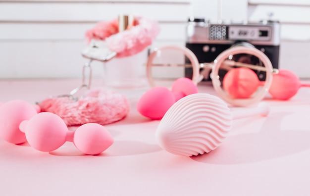 Женский розовый фон с разными секс игрушками
