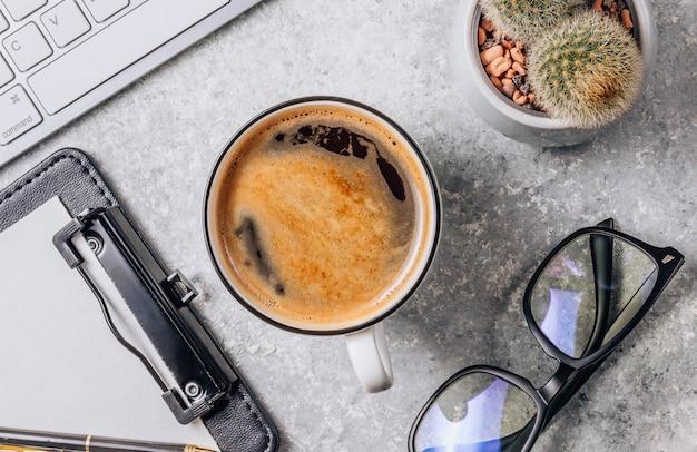 コンピューター、消耗品、一杯のコーヒーとサボテンのオフィスデスクテーブル