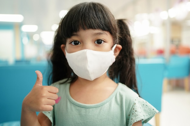 アジアの子供は親指で医療用マスクを使用します