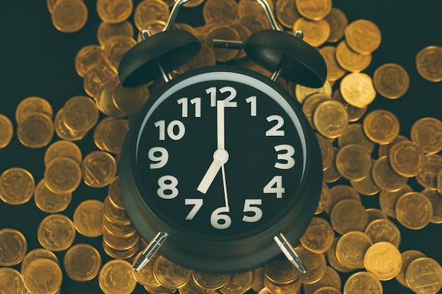 作業テーブルの上の目覚まし時計とコインスタック