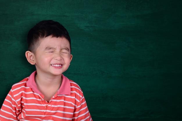 空の緑の黒板に笑って幸せなアジアの子供