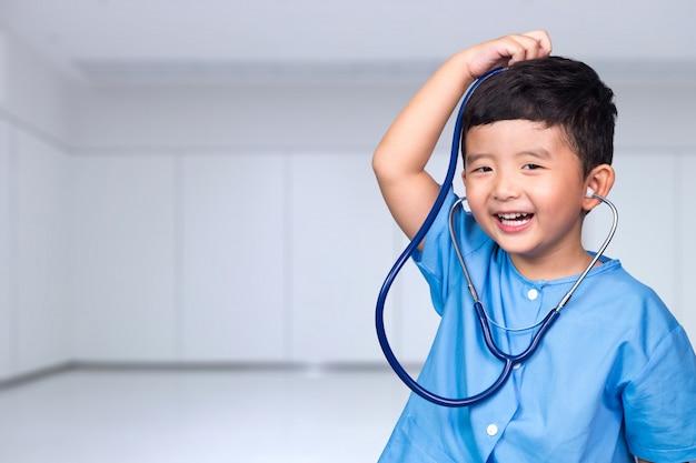 聴診器を保持している青い医療制服を着たアジアの子供の笑顔