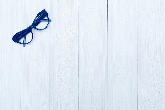 トップビューフラット横たわっていた、ウッドの背景にモダンな青い眼鏡