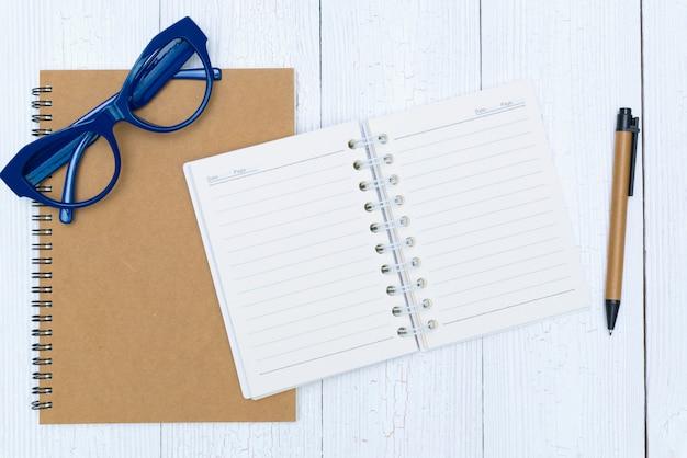 男の手がペンでノート用紙の空白のページに書く