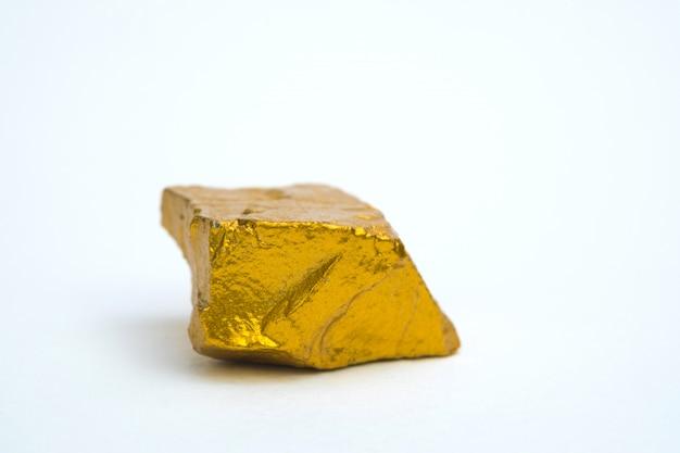 金ナゲットや白い背景の上の金の鉱石のクローズアップ