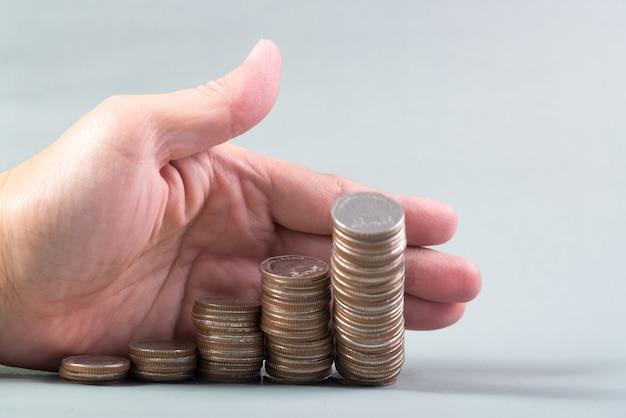 Рука толкает кучу монет, столбец монет падает