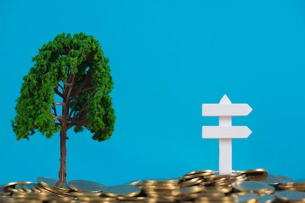 Дерево, растущее на куче золотых монет и белой деревянной доске знак