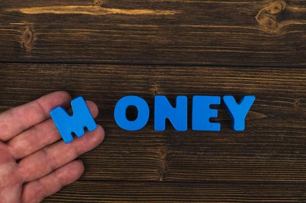 Рука и палец располагают текстовые буквы слова деньги
