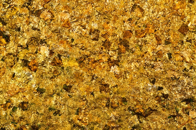光沢のある黄色の金箔や金箔の背景のスクラップ