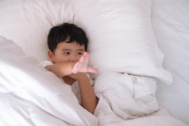 Азиатский мальчик дома на кровати