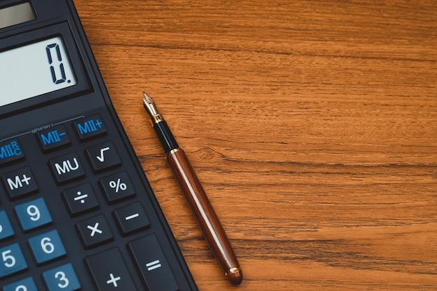万年筆や木の上の電卓とインクのペン