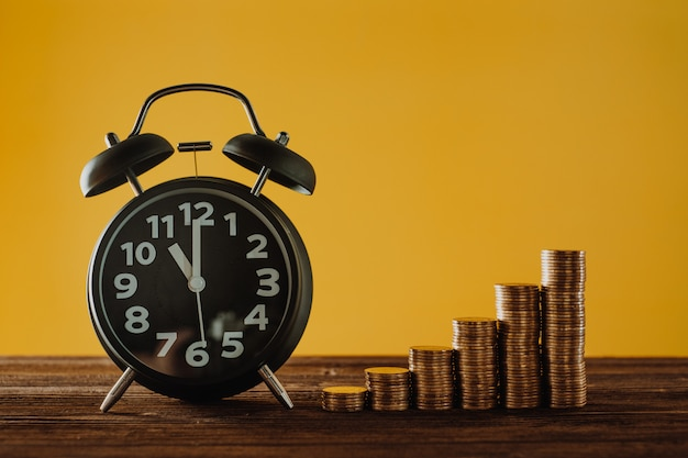 目覚まし時計と作業台上のコインスタックのステップ