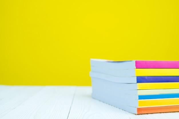 黄色と白いテーブルの上の本の山。