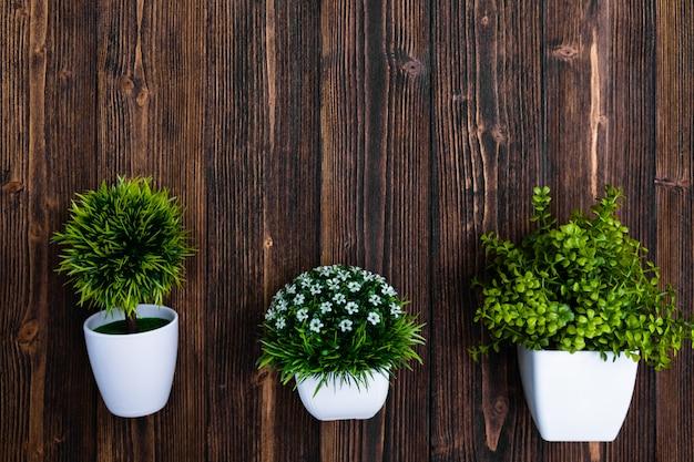ウッドの背景に白い花瓶の小さな装飾的な木と花の花束