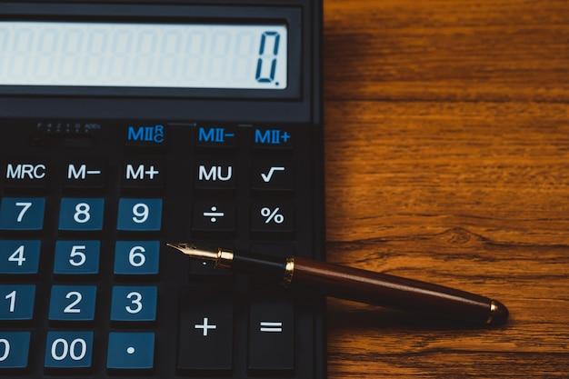 木の電卓と万年筆またはインクペン