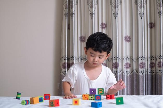 アジアの少年は自宅のベッドでおもちゃの正方形ブロックパズルを再生します