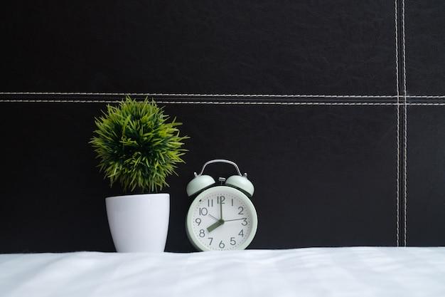ビンテージ目覚まし時計とベッドの上の小さな木
