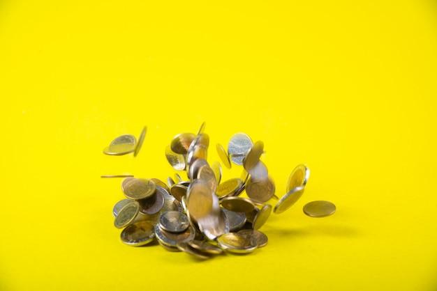 黄色の背景に落ちるコインお金
