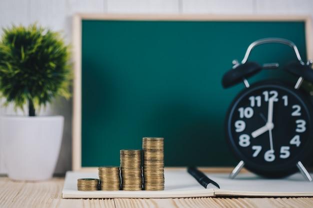 コインスタックと緑の黒板と目覚まし時計