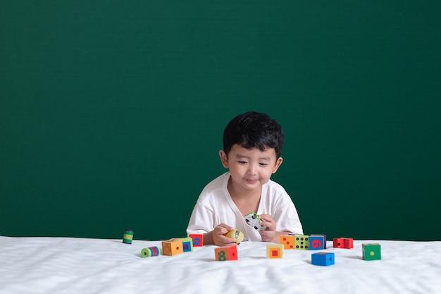アジアの少年は緑の黒板におもちゃや正方形のブロックパズルを再生します。