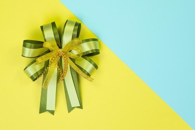 甘いパステルカラーの紙に装飾的な緑リボン弓