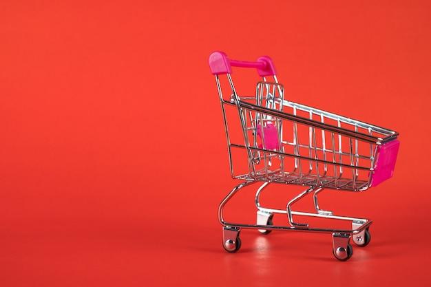 赤い背景の上のショッピングカートまたはスーパーマーケットのトロリー