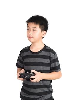 アジアの少年がヘリコプター、ドローンまたは飛行機のための無線リモコンハンドセットを保持