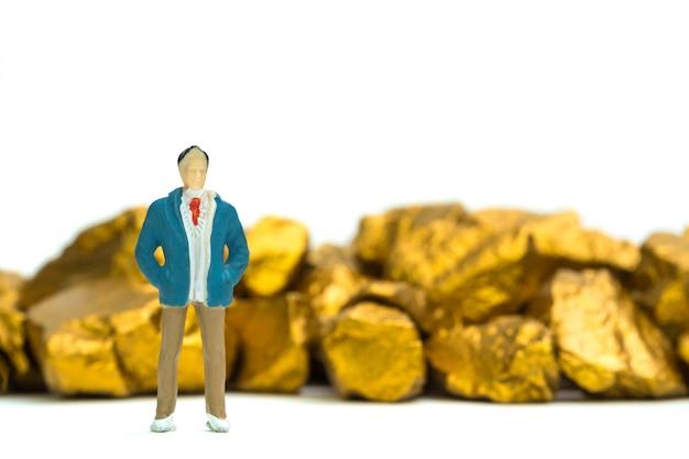 Фигурка миниатюрного бизнесмена с кучей золотых самородков