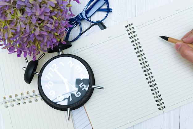 ペンでノート用紙の空白のページに書く人間の手