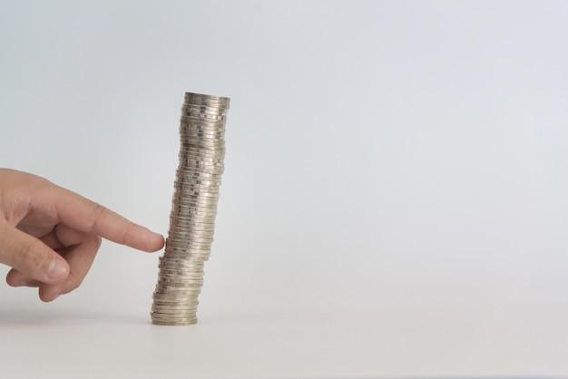 Палец толкает кучу монет