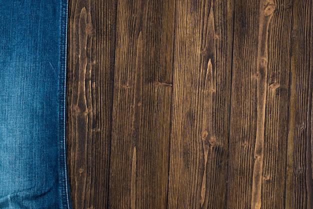 Коллекция потертых джинсов или джинсовой джинсовой ткани на грубом темном дереве