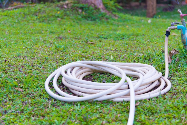 Садовый шланг или белая резиновая трубка с краном на траве поля.