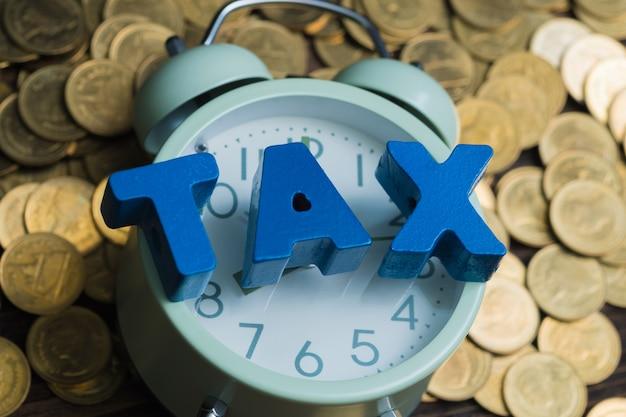 コインとビンテージの目覚まし時計のスタックと税アルファベット