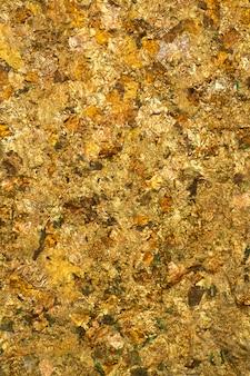 Блестящий лист желтого золота или обрывки золотой фольги