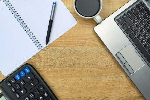 Портативный компьютер, калькулятор и чашка кофе на рабочем столе
