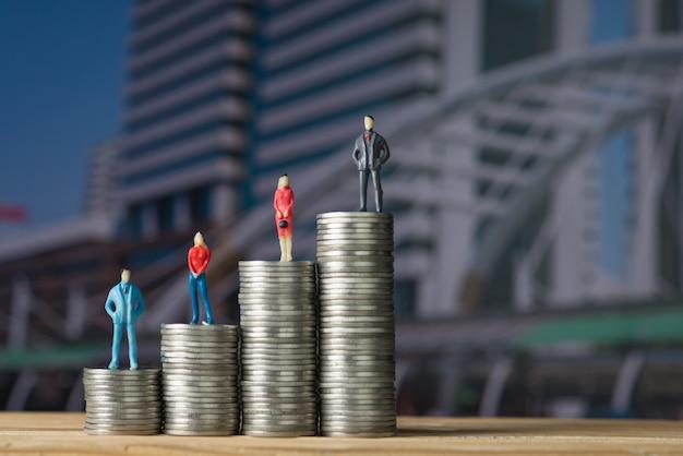 Рисунок миниатюрного бизнесмена, стоящего на стопке монет