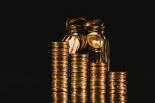ガラスの瓶の中のコインスタックとゴールドコインのお金