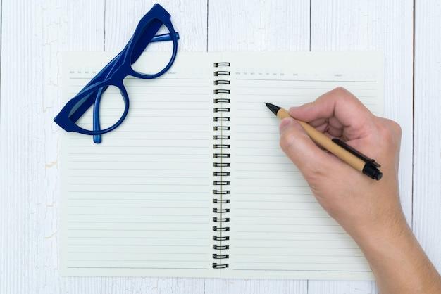 男の手がペン、メガネ、事務用品、トップビューでノートブック紙の空白のページに書く。