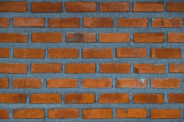 Красная предпосылка части кирпичной стены или текстура здания слоя кирпича.