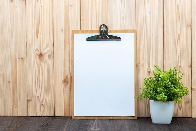 木製の背景に白い花瓶の小さなデコレーションツリーとクリップボード空白のホワイトペーパーシート