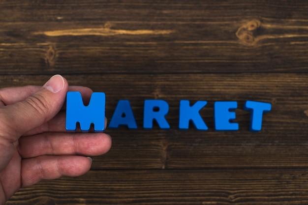 手と指は広告の単語や製品を追加するためのコピースペースで、木製のテーブルの上の市場単語のテキスト文字を配置します。