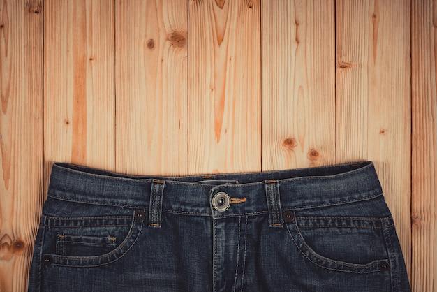 擦り切れているジーンズまたはブルージーンズデニムコレクションコピースペース、古いファッション概念と大まかな木製のテーブル背景に。